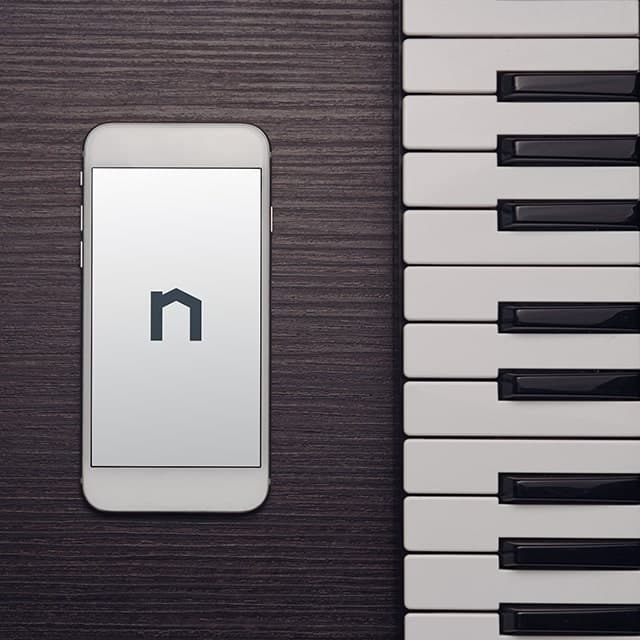 Next Moving logo in smartphone that is laying on top of the grand piano is representing Next Moving provide the best professional piano movers near me service in the market.